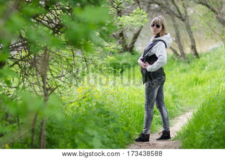 a girl on a forest glade stands on a path