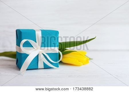 Packaged gift and yellow tulip. Concept of holiday birthday Easter March 8.