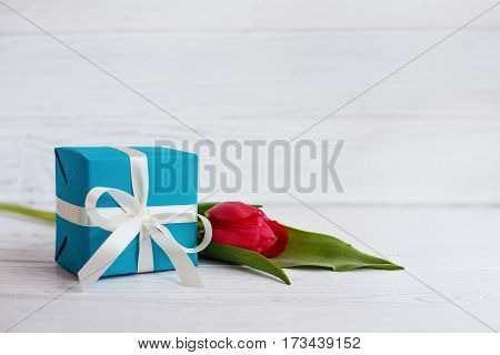 Packaged gift and red tulip. Concept of holiday birthday Easter March 8.