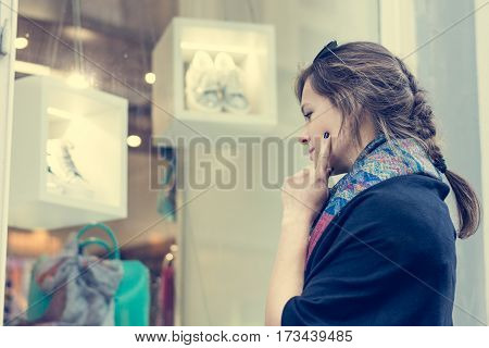 Young and attractive lady window shopping. Deciding what to buy. Customer in shopping street.