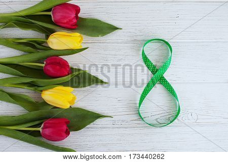Background with flowers tulips wooden white background. The concept congratulations on occasion of March 8 International Women's Day.