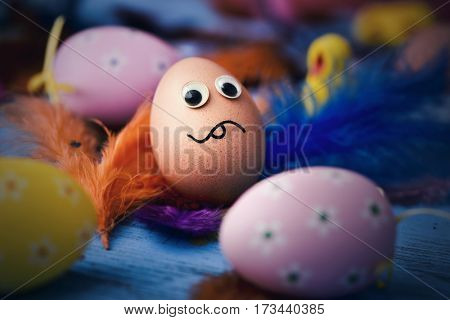 closeup of an easter egg ornamented with three-dimensional eyes and a drawn mouth, with a scared face, surrounded by feathers and more decorated eggs