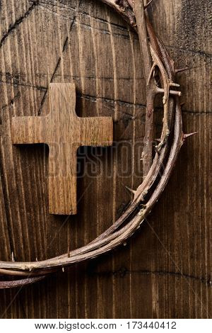 high-angle shot of a small wooden cross and a depiction of the crown of thorns of Jesus Christ on a wooden surface