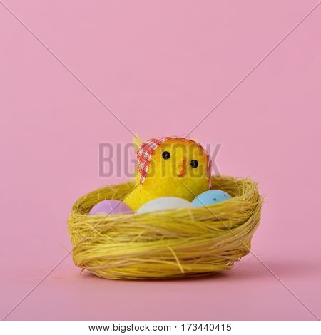 a teddy chick in a nest next to some eggs of different colors, against a pink background, with a blank space above it