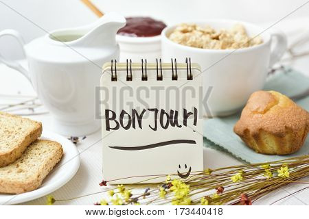 closeup of a table set for breakfast with a porcelain bowl with cereals, some toasts a bowl with jam and a note with the text bon jour, good morning written in french