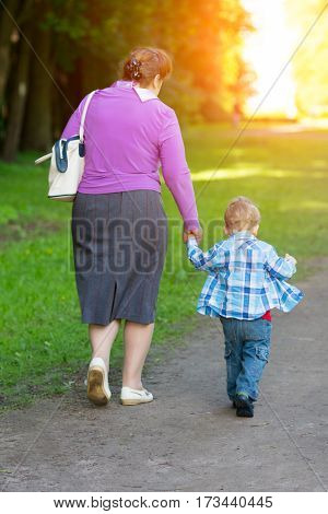 Grandmother walking with her grandson by the hand in the park.