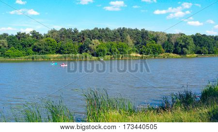 beautiful summer landscape with river and people riding on the water catamarans