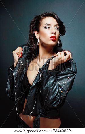 portrait of young passionate woman in black bra wearing leather jacket posing next to color background in photostudio