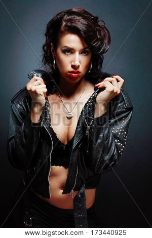 portrait of young woman wearing leather jacket posing next to color background