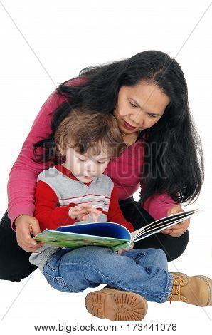 A Filipino nanny sitting with a little boy on the floor and read the story to him isolated for white background.