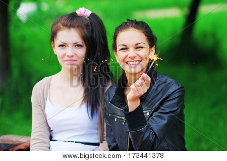 Portrait of a happy young women with long dark hair. Two beautiful girlfriend was found in the summer on holiday and having fun igniting sparklers.
