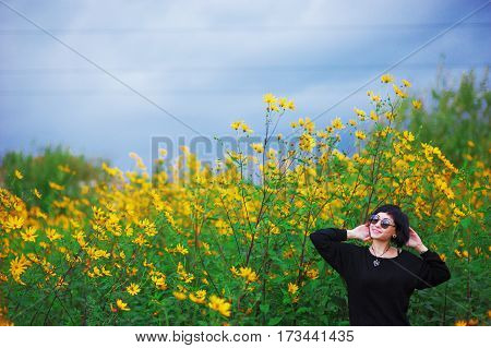 Young interesting girl in a black dress and glasses on a beautiful meadow of yellow flowers of Jerusalem artichoke.