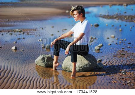 Young modern girl in a white blouse and black pants sitting on a rock dropping his bare feet into the water and meditates closing his eyes. Around water sand and stones.
