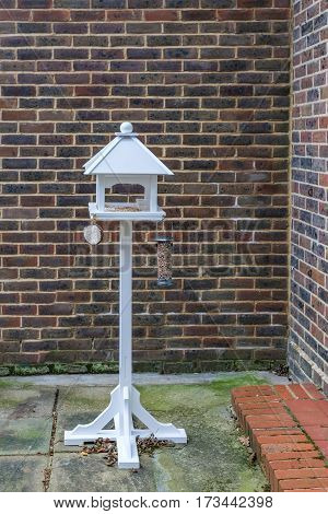 Bird Table. Full length bird table standing on a patio and set up for attract wild birds to come and feed.