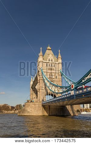 Vertical shot of half of Tower Bridge with the river and a blue sky on a bright afternooon in spring.