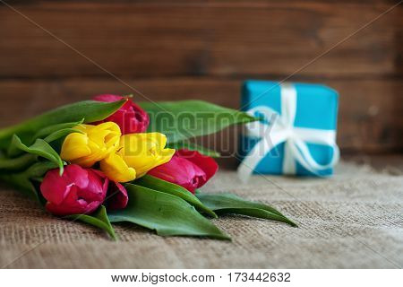 Spring tulips and blue gift. Greeting. Concept of holiday birthday Easter March 8.