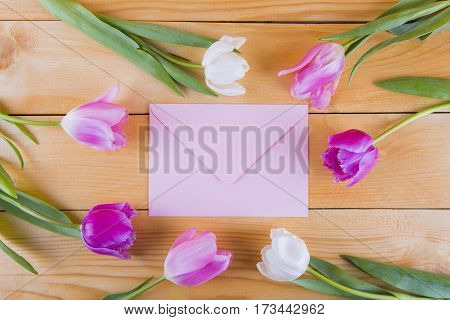 Bouquet Of Tender Pink Tulips With Pink Envelope On Light Wooden Background
