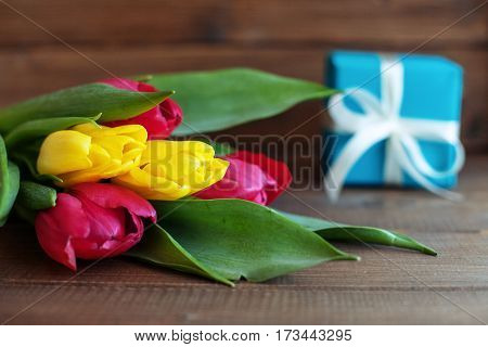 Colored tulips and blue gift on wooden background. Concept of holiday birthday Easter March 8.