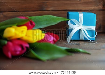 Colored tulips and blue gift on dark wooden background. Concept of holiday birthday Easter March 8.