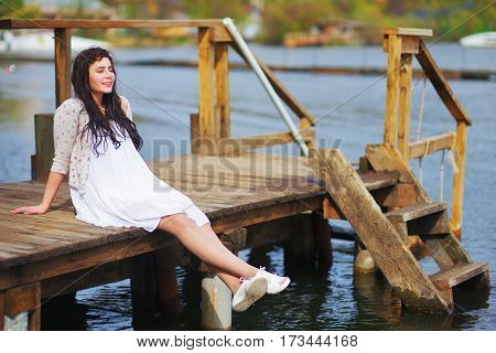 Adorable smiling long-haired brunette girl in a white dress and beige knitted cardigan sitting on wooden dock over the water with my eyes closed and enjoying warm spring Sunny day side view.