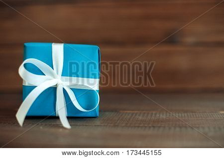 Blue gift with ribbon on a wooden background. Concept of holiday birthday Easter March 8..