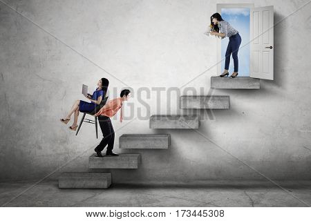 Picture of angry boss shouting through a megaphone while commanding her worker to walk upwards on the stairway
