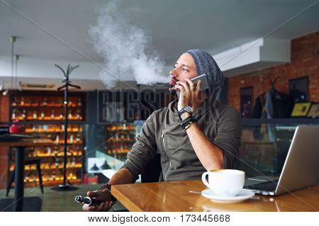 Young handsome hipster man with beard sitting in cafe with a cup of coffee. vaping and releases a cloud of vaporsitting. Talking mobile phone and having a little break.