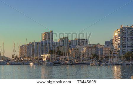 Late afternoon sun falls on marina boardwalk & bay in St Antoni de Portmany,  Ibiza,  Balearic Islands, Spain.  Sun glints off condo building glass in town.