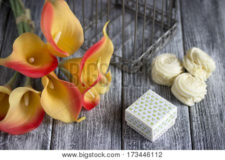 Orange Yellow Calla Lilies Bouquet With Marshmallow And Cardboard Box On A Gray Wooden Background