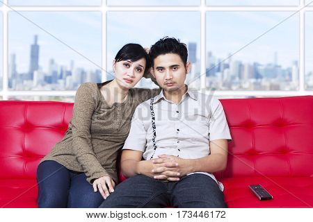 Bored young couple watching television at apartment with cityscape background