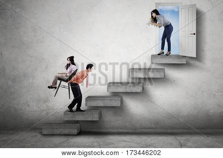 Female boss yelling through a megaphone while commanding her employees to walk upward on the stair
