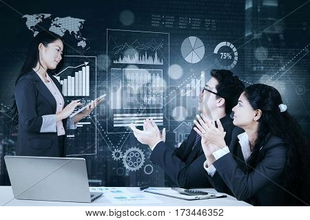 Image of business people giving applause on their manager after presentation with virtual finance chart