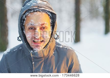young man in a anorak covered in snow in winter forest at sunset. Snowflakes lie on the eyelashes eyebrows cheeks.