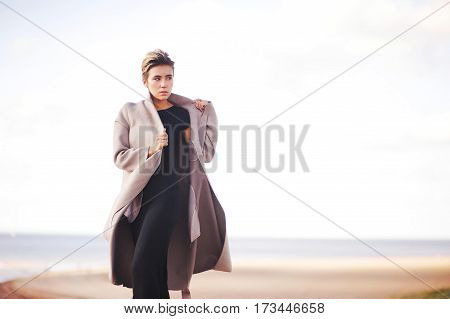 Portrait of confident business woman in elegant coat and dress running along the coast