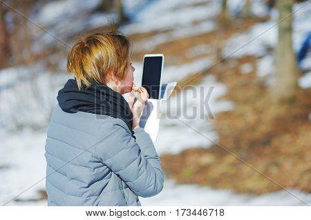 young attractive girl in a grey jacket looking at the screen of a modern smartphone in a snowy Park