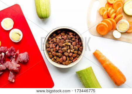 healthy dogfood with sliced eggs, fresh vegetables and raw meat on white kitchen table background top view