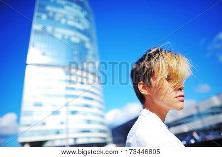 Portrait of modern business woman around a multi-storey office buildings in the cityscape.
