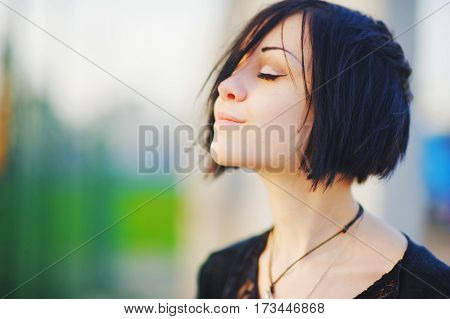 Portrait of young pretty woman brunette with closed eyes relaxing bright warm day on blurred background close up.