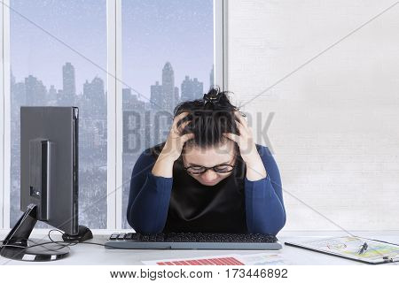 Businesswoman holding her head while feeling dizzy with financial chart on the desk winter background on the window