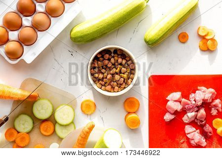 Dogfood set with fresh vegetables, eggs and raw meat on white table background top view