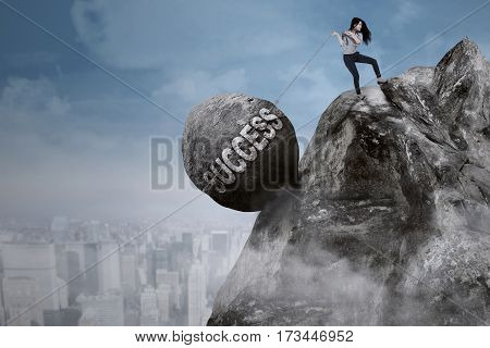 Young Asian businesswoman is pulling big rock with success word while climbing on the cliff