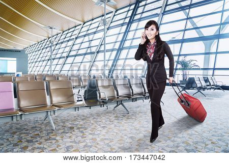 Image of beautiful young businesswoman carrying a luggage and talking by mobile phone while walking in the airport terminal