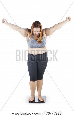 Full length of cheerful overweight woman with blonde hair standing on a weighing scale while expressing her success to lose weight