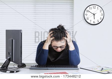Female entrepreneur feels dizzy with financial chart on the desk while holds her head