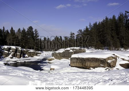 Wide view of a snowy country landscape with a small stream of rapids running through rock faces on either side and a background of green fir trees at Pabineau Falls near Bathurst, New Brunswick, on a bright sunny day with blue skies and clouds in February