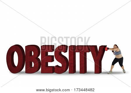 Fat woman wearing boxing gloves while punching stones shaped word of obesity