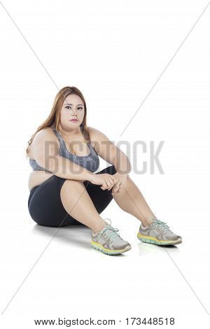 Portrait of a fat woman sitting on the floor in the studio while wearing sportswear after exercising isolated on white background