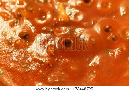 A macro photo of cooking tomato sauce.