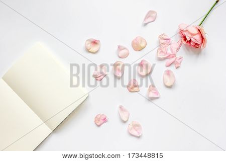 trandy woman design with flower petals and copybook on white table background top veiw mock-up