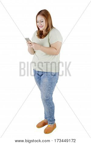 Full length of obese girl with blonde hair standing in the studio while using her cellphone. Isolated on white background